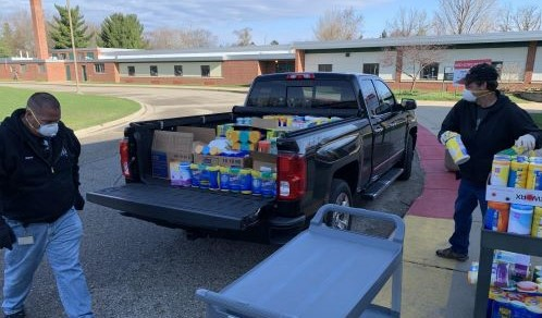Employees loading supplies into a pick-up truck at the elementary.